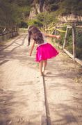 Rear view of little girl in pink dress walking Stock Photos