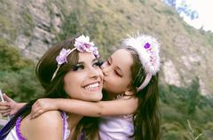 Beautiful little girl wearing a fairy costume kissing her mom - stock photo