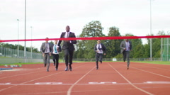 4K Group of competitive businessmen racing to the finish line at running track Stock Footage