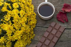 chocolate, red leaf, bouquet of yellow flowers and coffee, on a wooden table - stock photo