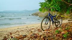 Blue Mountain Bike on a Rocky Tropical Beach Stock Footage