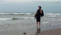 Businesswoman walking along an ocean beach Stock Footage