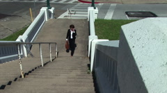 Businesswoman walking up an outside set of stairs Stock Footage
