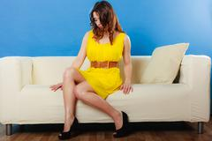 Girl fashionable dress high heels sitting on couch. Stock Photos