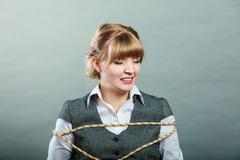 Afraid kidnapped woman tied with rope to chair. Stock Photos