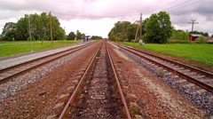 The rail tracks on the side of the green fields Stock Footage