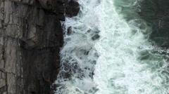 Aerial looking down on breaking waves against rocks Stock Footage