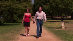 Couple walking down a exercise path Stock Footage