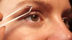 Woman tweezing eyebrows depilating with tweezers 4K Stock Footage
