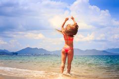 Blonde slim gymnast in bikini stands backside on edge of sea Stock Photos
