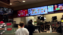 People ordering food at mcdonalds check out counter inside Walmart store Stock Footage