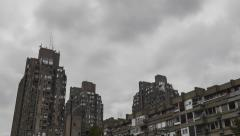 4K time lapse of moving clouds above concrete buildings block Stock Footage
