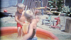 1963: Brother intimidating threatening with bucket of water in summer child - stock footage