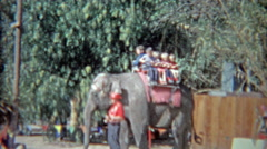 1963: Kids riding on Asian elephant at amusement park ride for privileged Stock Footage