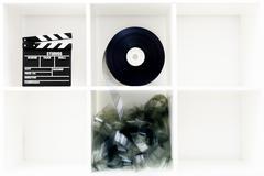 Movie clapper board and film reel on white bookshelf - stock photo