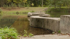 Concrete walkway through the river. Autumn daytime. Smooth dolly shot. Stock Footage