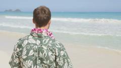 Male Tourist Standing On Hawaiian Beach Wearing Flower Lei - stock footage