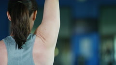4K View from behind of unrecognisable woman training with weights at the gym Stock Footage