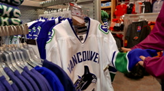 Woman picking one of Reebok Vancouver Canucks cloth Stock Footage