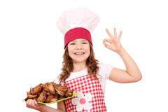 Happy little girl cook with roasted chicken wings and ok hand sign Stock Photos