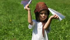 Cute boy in the old helmet pilot playing with paper plane Stock Footage