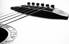 Acoustic guitar focus on bridge and strings Stock Photos