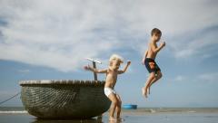 Adorable children having fun on sand beach on blue sky, sea background. Vietnam Stock Footage
