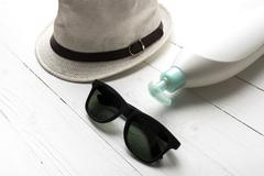 hat sunglasses and body lotion - stock photo
