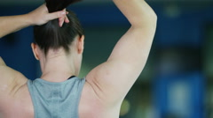 4K View from behind of unrecognisable woman tying back her hair at the gym - stock footage