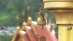 Small bronse buddhist bell, that is swaying by the wind and roof of buddhist tem Stock Footage