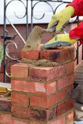 Bricklayer laying brick Stock Photos