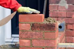 Bricklayer laying brick - stock photo