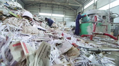 Workers dumping paper in recycling factory Stock Footage