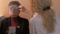 Doctor ophthalmologist determining diopter on eyes of older woman, no grading,4K - stock footage