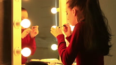 Stock Video Footage of Young woman applying mascara in front of a mirror