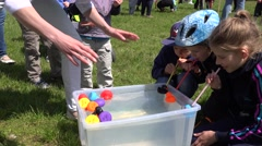Children with straw play duck race in plastic water pool. 4K Stock Footage