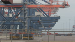 Large harbor cranes loading container ships in the port of Rotterdam Stock Footage