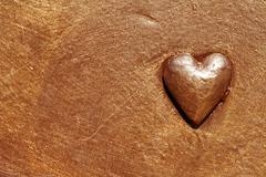 beautiful heart of metal painted in gold paint - stock photo