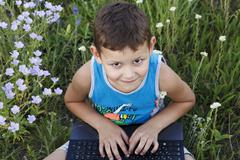 little boy enjoys a laptop on nature - stock photo