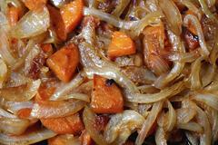Fried onions and carrots in the pan, a bright background Stock Photos