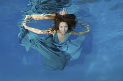 Woman in a long white dress under water underwater fashion in the pool Odessa Kuvituskuvat