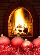 Red Christmas balls and tinsel with fireplace Stock Photos