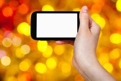 Hand with smartphone on christmas background Stock Photos