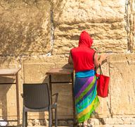 Stock Photo of Unidentified tourist in a bright red jacket at the Western Wall
