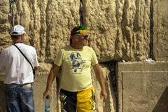 Stock Photo of Unknown tourist in yellow shorts at the Western Wall