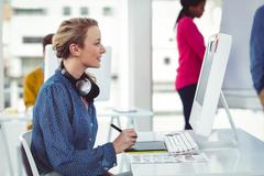 Stock Photo of Graphic designer wearing headphones at desk