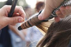 master hairdresser and stylist in the working process - stock photo