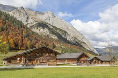 Almdorf Eng huts in front of autumnal forest and mountain range EngAlm - stock photo