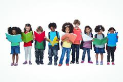 A row of children standing together reading books - stock photo