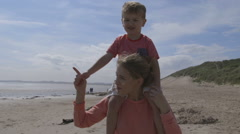 Young mother and son walking along the beach - stock footage